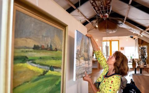 Anje Wester-Koopmans in Galerie Koopmans bij het werk van haar vader en broer.