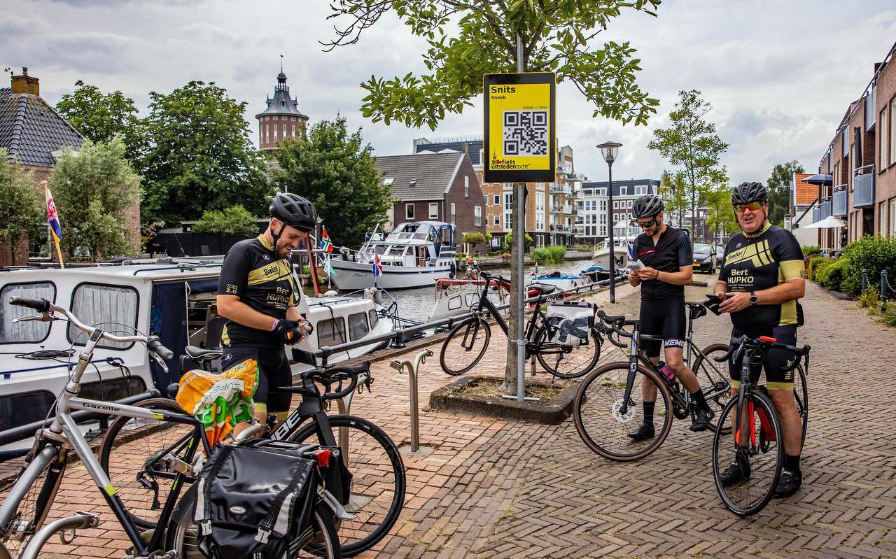 Drie fietsers uit België scannen in Sneek de QR-code.