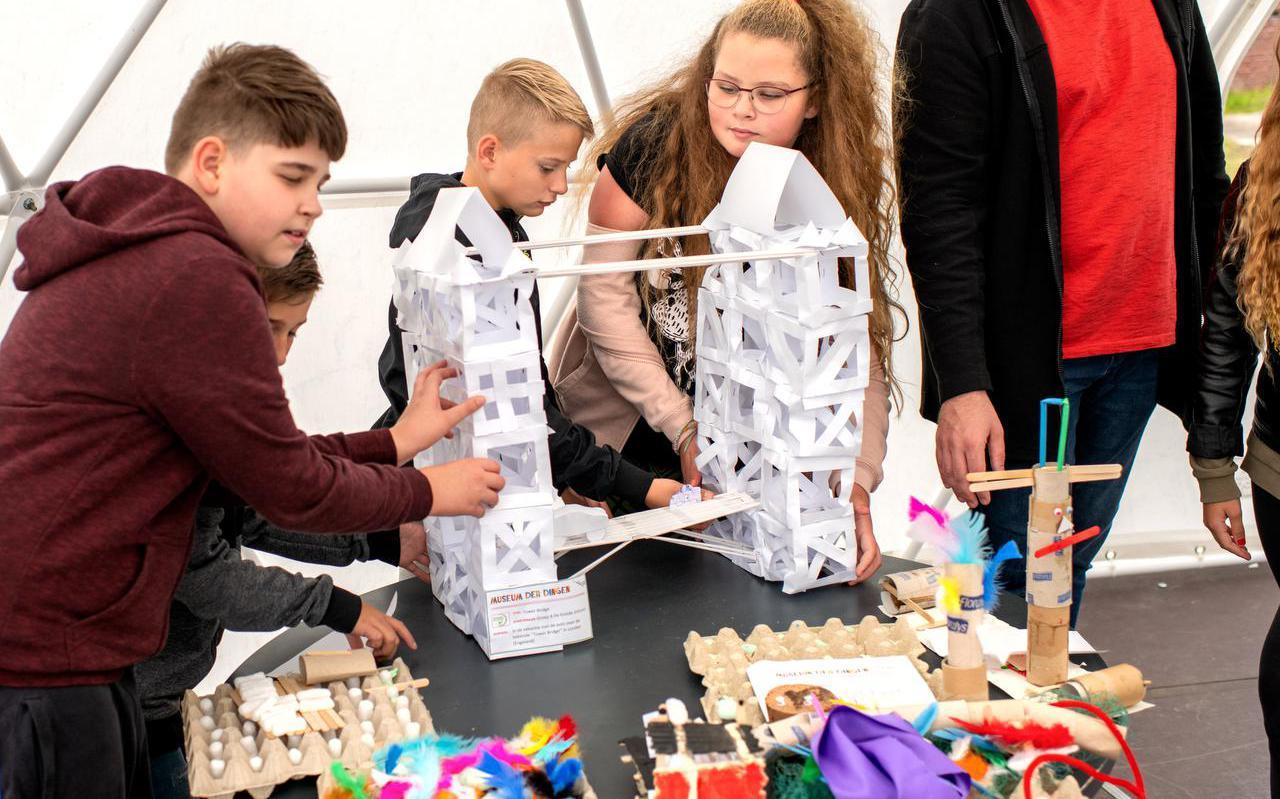 Leerlingen van groep 8 van De Greide uit Jistrum bergen hun kunstwerken naar het tijdelijke museum Cultuurschool Het Achterland op de Burgumerdaam.