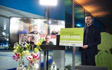 Wethouder Jelle Zoetendal toont een van de cheques. Vertegenwoordigers van de vijf winnende duurzaamheidsprojecten zijn op het scherm te zien.