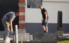 Steenhouwer Ben Seldenrijk (rechts) en een medewerker lichten de grafsteen van Eise Eisinga.