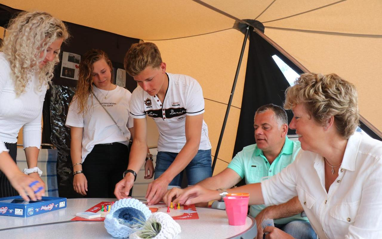 """Van links naar rechts: Melissa, Nienke, Wessel, Gerwin, Karin. Op de voorgrond de gehaakte schelpen. Het gezin speelt hier het Keezenspel. ,,De kinderen hebben de liefde voor het eiland overgenomen"""", aldus Karin."""