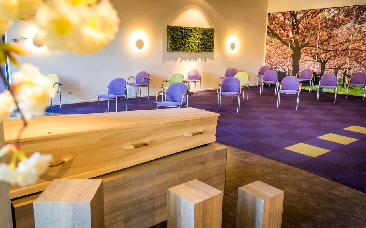 Stoelen staan 1,5 meter uit elkaar in de aula van een uitvaartcentrum.