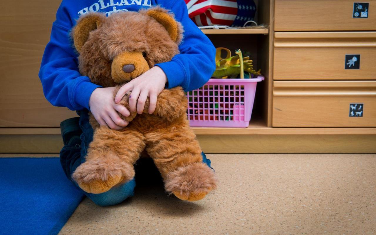 Een jongen met een knuffelbeer in een speelkamer van een jeugdhulpverleningscentrum.