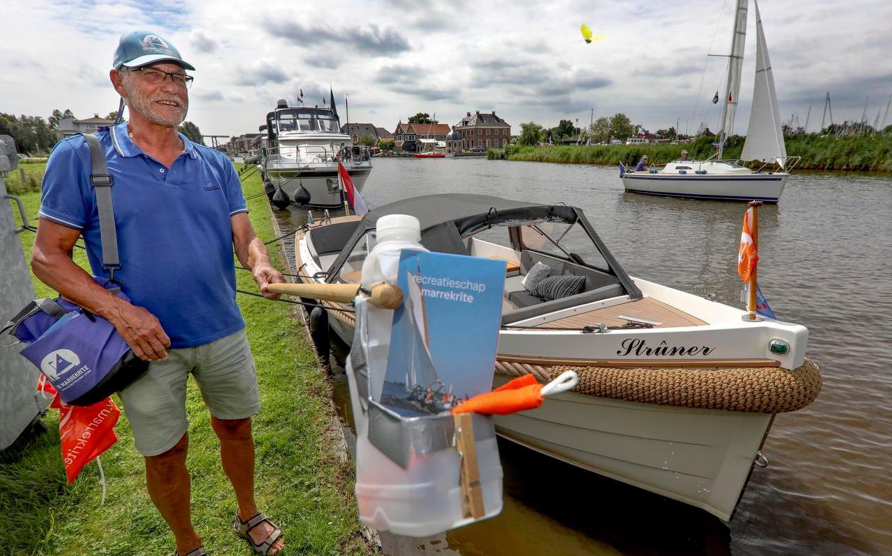 Vrijwilliger Sjoerd Groen verkoopt Marrekrite-wimpels bij de Noarder Ie.