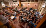 De dertig leden tellende fanfare repeteert met het reünieorkest de jubileumcompositie voor De Kriich in het dorpshuis van Wergea.