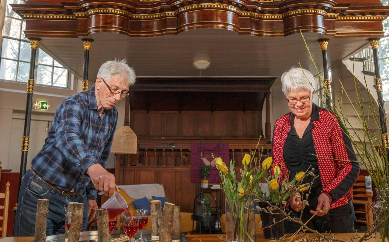 Dieuwke van der Weerd en Pieter Mulder zijn bezig met het liturgisch bloemstuk in de Dorpskerk.
