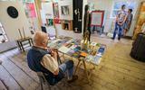 Een bezoeker gaat helemaal op in de boekentafel in een van de wonderkamers. Beeldend kunstenaar Sigrid Hamelink lijmde er een aantal titels uit haar eigen collectie op vast.