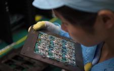 Een medewerker van een Chinese fabriek voor smartphones bekijkt printplaten met microchips.
