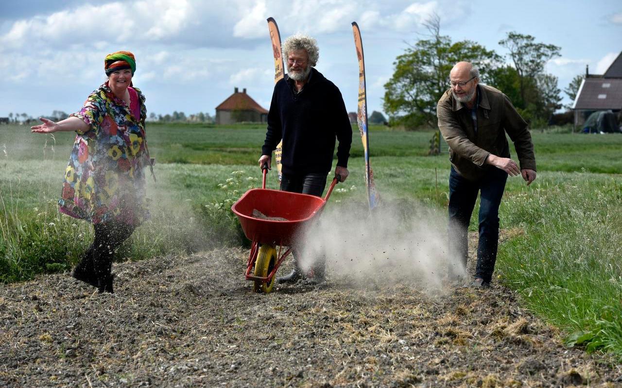Margaretha Posthumus, Marten de Boer en Gjalt Faber (vanaf links) zaaien de Gjalt Faberberm langs de Hoptilstersdyk bij Hesens in met bermbloeiers.