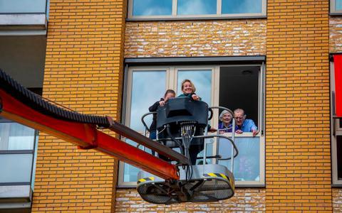 Kleinkinderen Janny en Ytsje vieren het huwelijksfeest van pake en beppe Oebele en Jantsje Kooistra mee vanuit de hoogwerker.