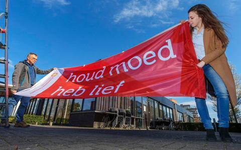 Ds Anne-Meta Kobes en Tonny van Balen, beheerder van kerkgebouw Trinitas in Heerenveen, met een vlag 'Houd moed, heb lief'.