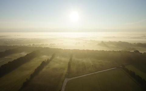 Luchtfoto van een opkomende zon in de mist boven Friese weiden.