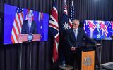De Australische premier Scott Morrison kondigt het AUKUS-bondgenootschap aan, geflankeerd door de Britse premier Boris Johnson (l) en de Amerikaanse president Joe Biden op beeldschermen.
