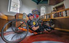 IJsbrandus van Popta op zijn handbike. Hij fietste deze zomer langs 54 Friese kerken.