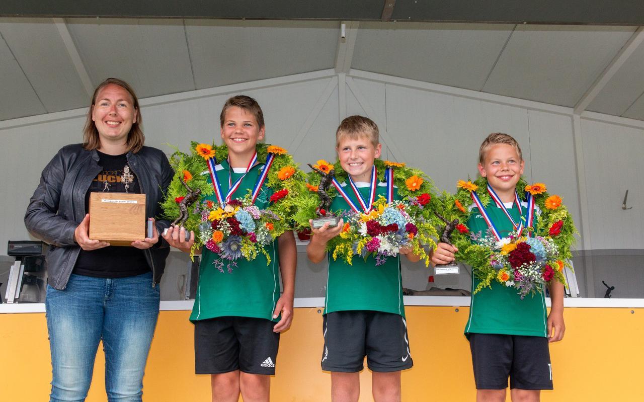 Coach Grada van der Schoot is trots op (van links af) Rudmer Faber, Melle Talsma en Harmen Faber na de winst van Achlum op de jongens pupillenbond in buurdorp Arum.