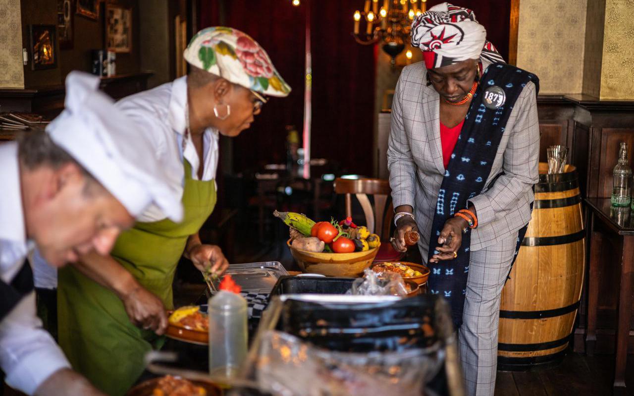 Marian Markelo van het Nationaal Instituut Nederlands Slavernijverleden en Erfernis (r) schept heri heri op, bereid door koks Reitse Spanninga (l) en Judith Cyrus (m).