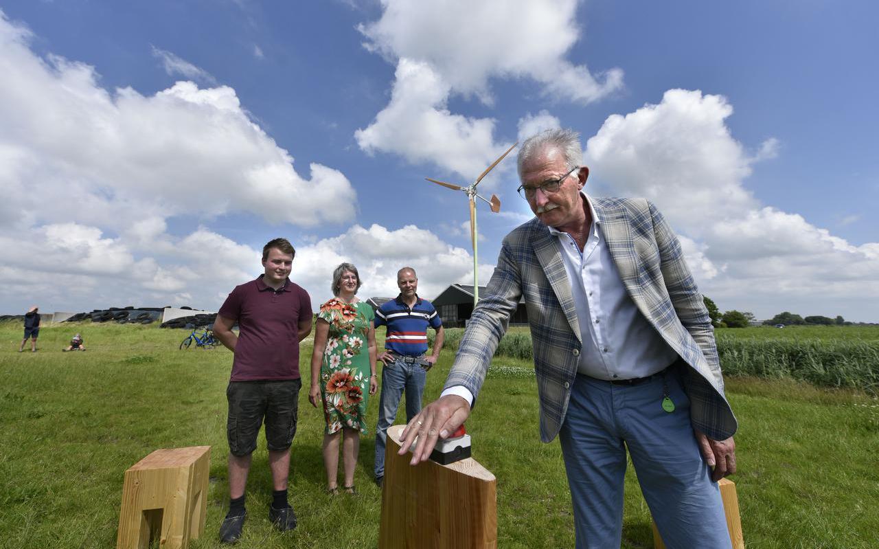 Wethouder Jan Dijkstra zet de eerste boerenwindmolen van Fryslân in werking op het bedrijf van (vanaf links) Sietse de Boer en Wietske en Germ de Boer.