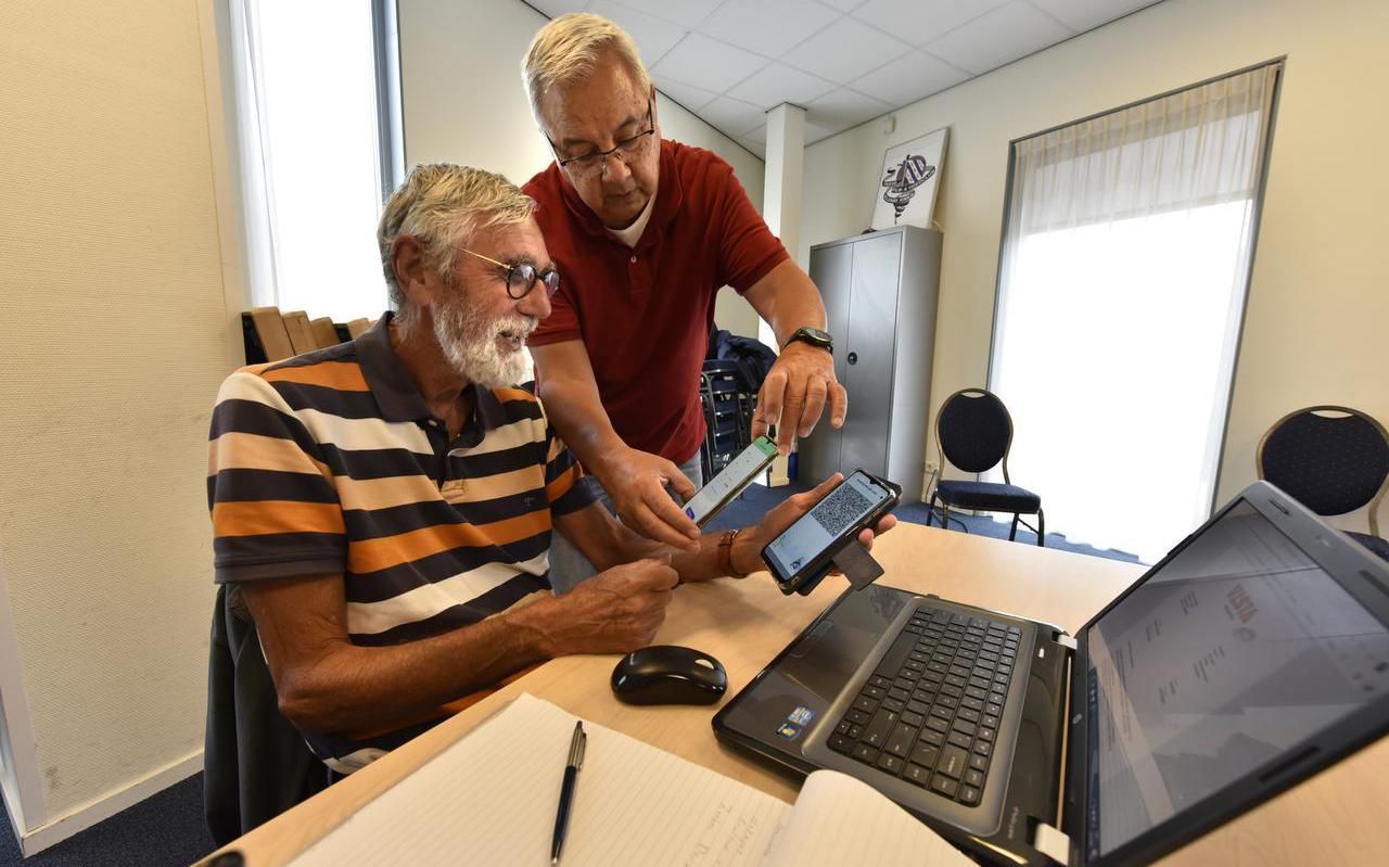 Gabe Westra (79, links) krijt uitleg over de corona-app van Evert Slok Soede.