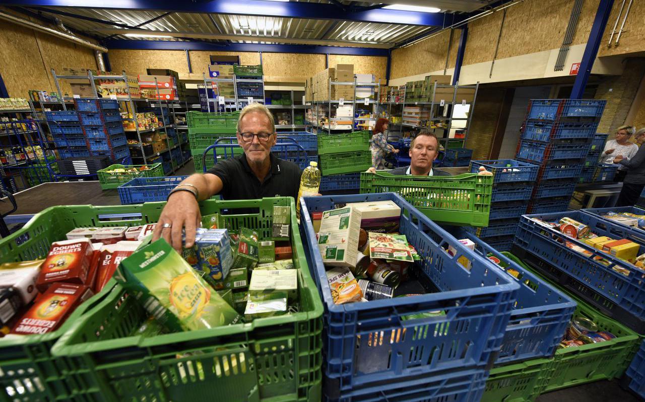 De voedselbank Leeuwarden in betere tijden. Vrijwilligers verdelen voedsel over de kratten.