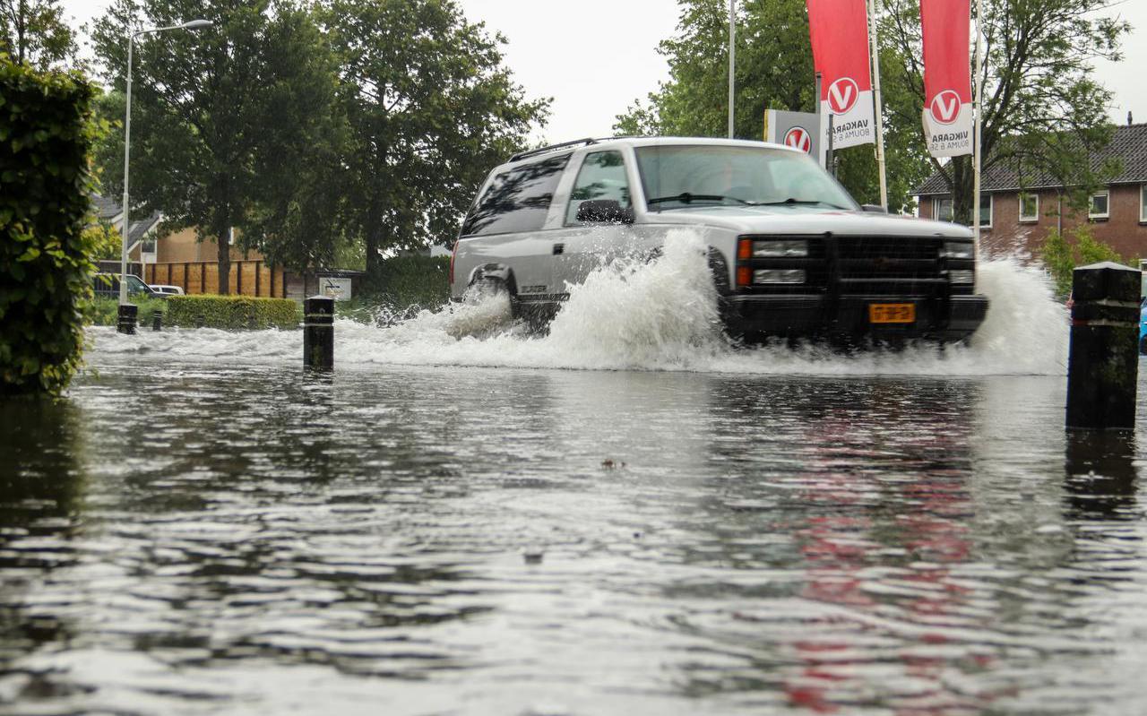 Ondergelopen straten in Burgum door zware regenbuien.