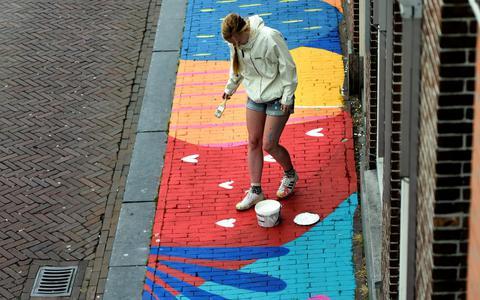 Carlijn Lenten beschildert de stoep aan het einde van de Voorstreek tussen ijswinkel La Venetia en de Jumbo Supermarkt.
