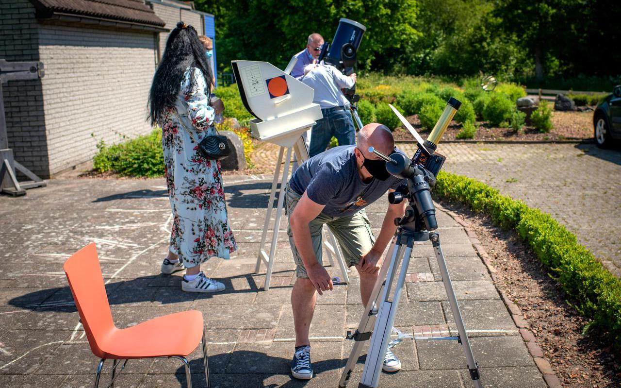 Bezoekers van volkssterrenwacht Observeum in Burgum kijken door telescopen naar de gedeeltelijke zonsverduistering.