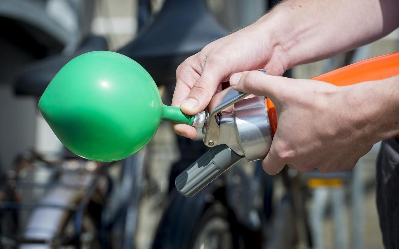Een lachgaspatroon wordt via een speciale spuitbus in een ballon geleegd.