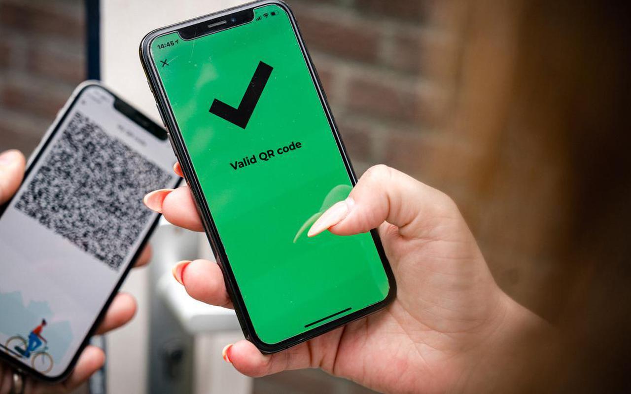 Een telefoon met een groen vinkje in de CoronaCheck-app.