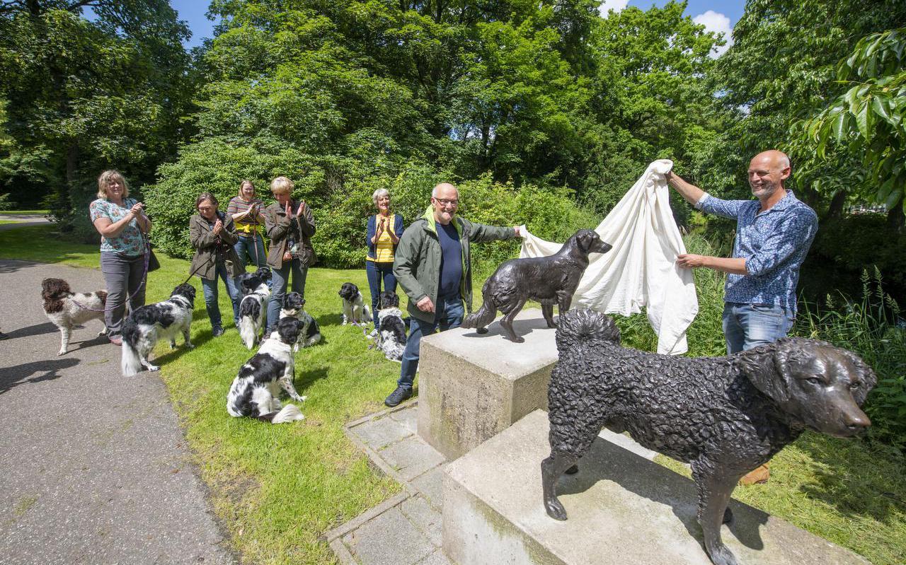 Hans Jouta (r) en Dick Vermeij onthullen de herstelde sculptuur Us Hûnen aan de rand van het Rengerspark in Leeuwarden.