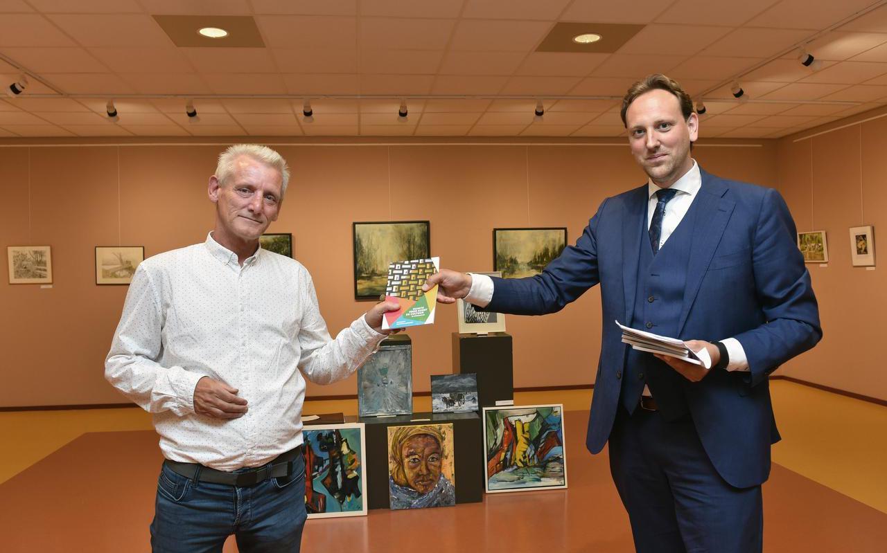 Wethouder Roelof Theun Hoen (rechts) overhandigd het eerste exemplaar van  'Ruimte voor kunst en cultuur in coronatijd' aan Gerrit van de Meeberg die de schilderwedstrijd had georganiseerd.