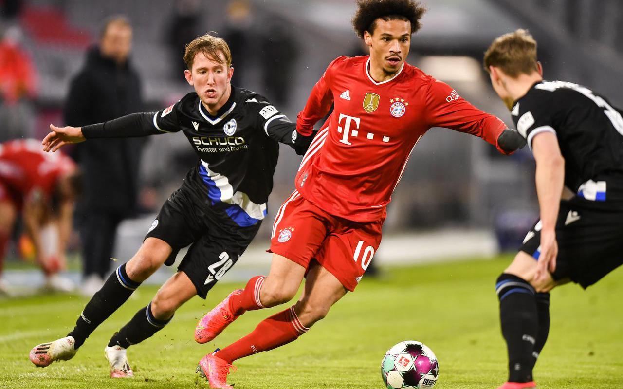 Michel Vlap (l) probeert namens Arminia Bielefeld Leroy Sané (Bayern München) af te stoppen.